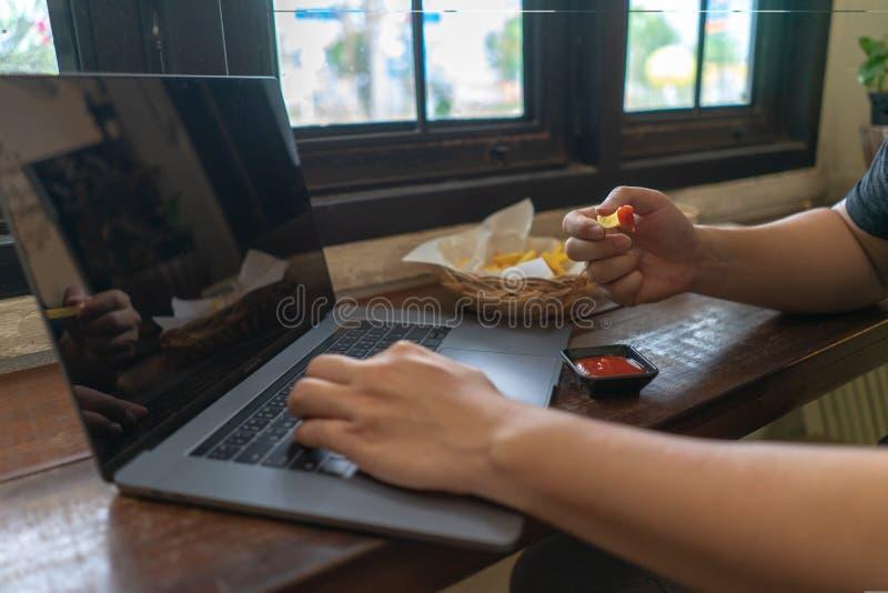 Homem de negócio que usa o laptop, o teclado de datilografia do caderno da mão e comer batatas fritas do fast food com ketchup se fotos de stock