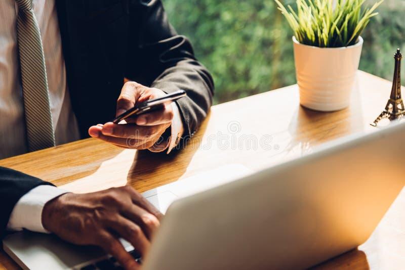 Homem de negócio que usa o telefone esperto móvel da tecnologia com COM do portátil foto de stock