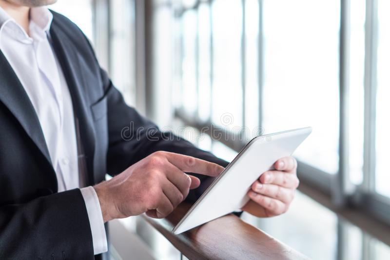 Homem de negócio que usa a tabuleta pela janela imagem de stock royalty free