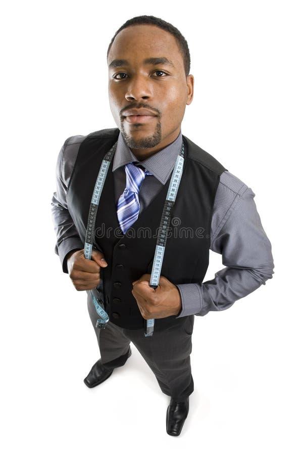 Homem de negócio que usa uma fita de medição fotografia de stock