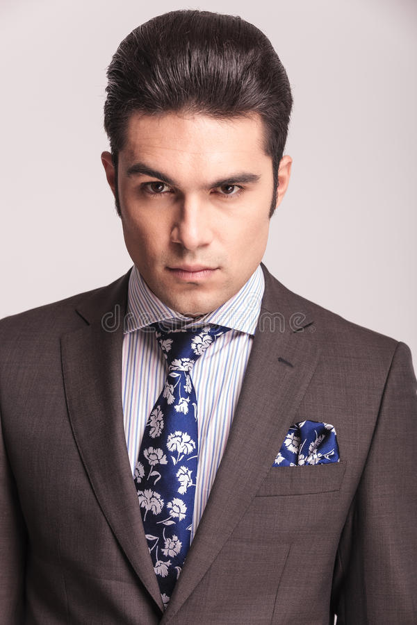 Homem de negócio que veste um terno cinzento e um laço azul fotografia de stock royalty free