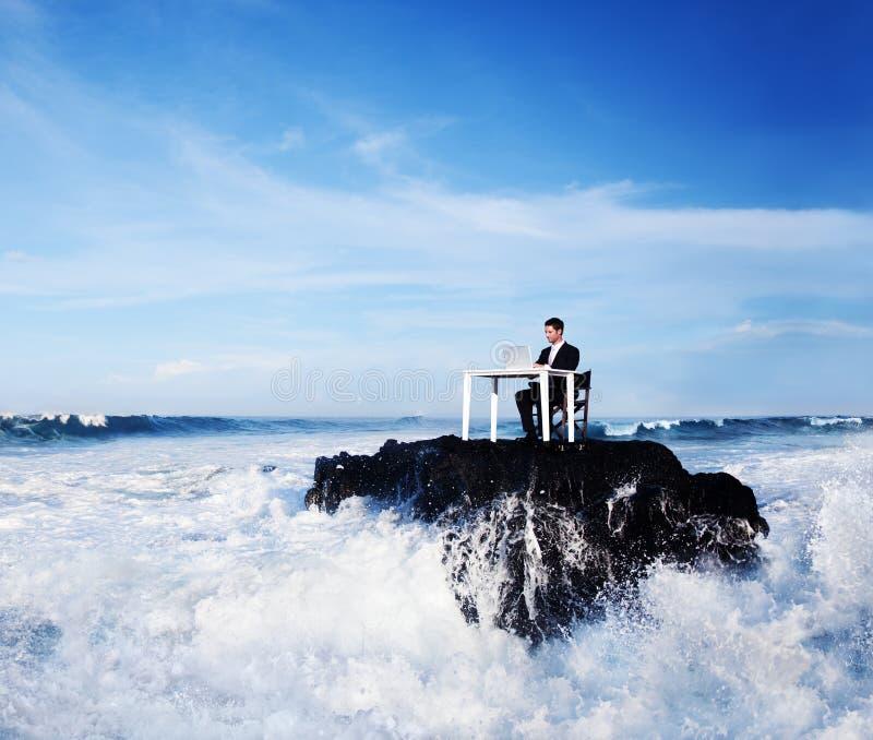 Homem de negócio solitário que trabalha em uma rocha remota imagem de stock royalty free