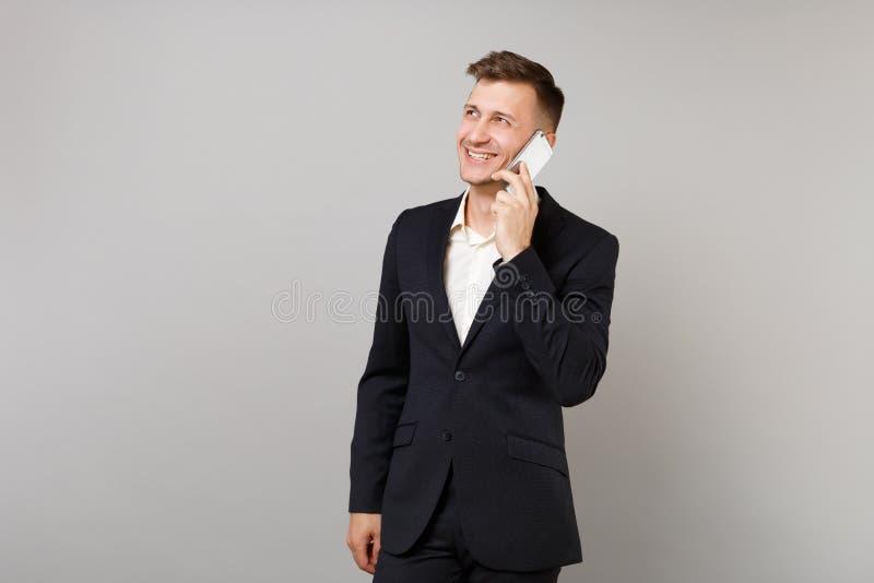 Homem de negócio de sorriso no terno clássico que olha de lado a fala no telefone celular que conduz a conversação agradável isol foto de stock royalty free