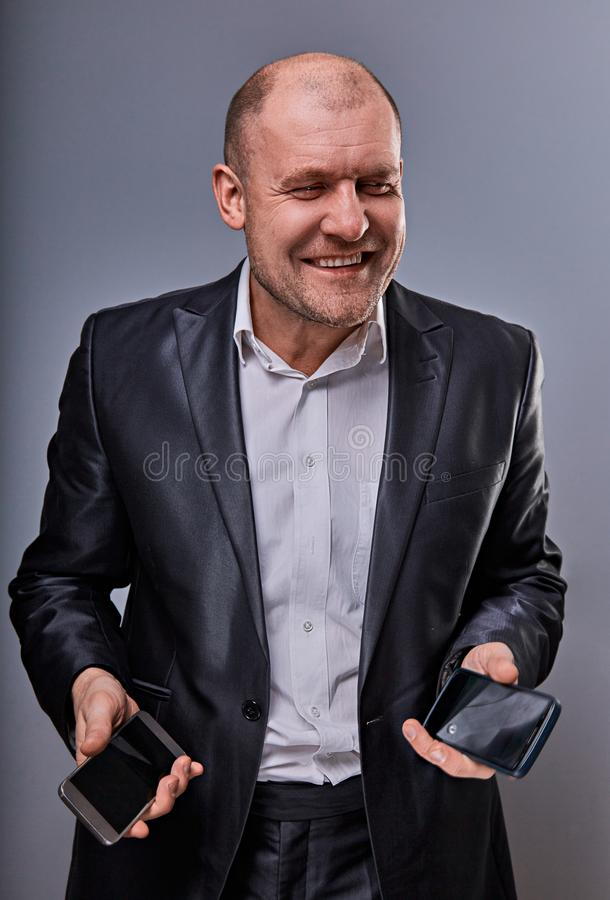 Homem de neg?cio de sorriso positivo que fala em dois telefones celulares muito emocionais no terno do escrit?rio no fundo cinzen fotografia de stock