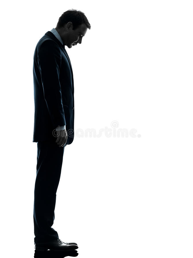 Homem de negócio triste que olha abaixo da silhueta imagem de stock royalty free