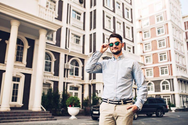 Homem de negócios à moda nos óculos de sol no quarto britânico Guarda a mão no bolso, sorrindo à câmera foto de stock