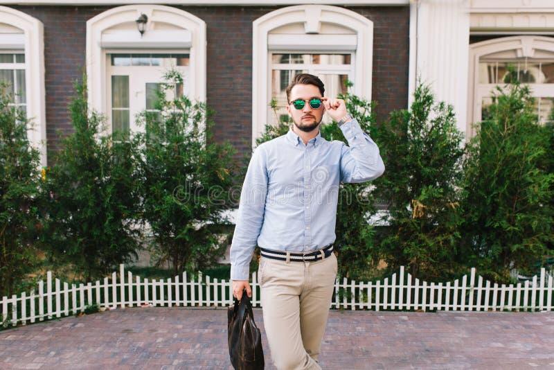 Homem de negócios à moda nos óculos de sol que anda em torno do quarto britânico Guarda o saco do blag, olhando à câmera imagem de stock royalty free