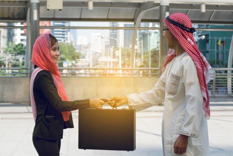 Homem de negócios árabe e mulher de negócios que guardam o saco imagens de stock