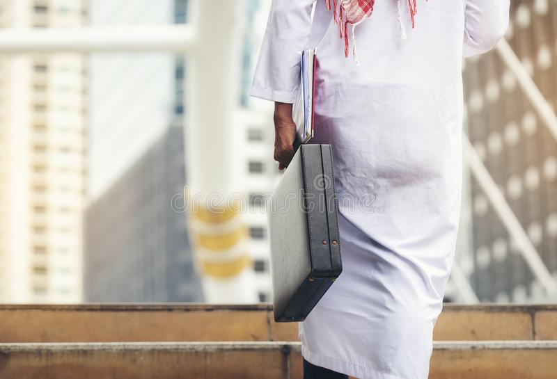 Homem de negócios árabe que guarda uma pasta que anda acima das escadas no th foto de stock royalty free
