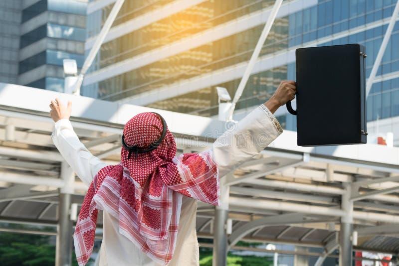 Homem de negócios árabe que mantém o saco bem sucedido imagens de stock royalty free