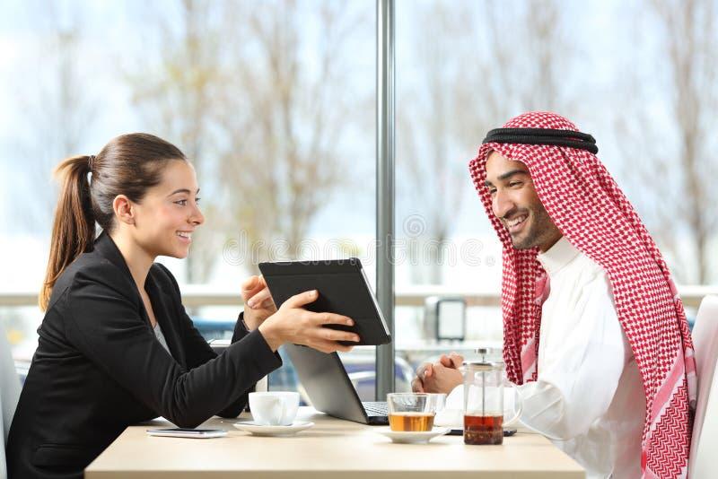Homem de negócios árabe que trabalha com seu colega de trabalho foto de stock