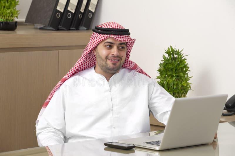 Homem de negócios árabe que trabalha no portátil no escritório imagens de stock royalty free