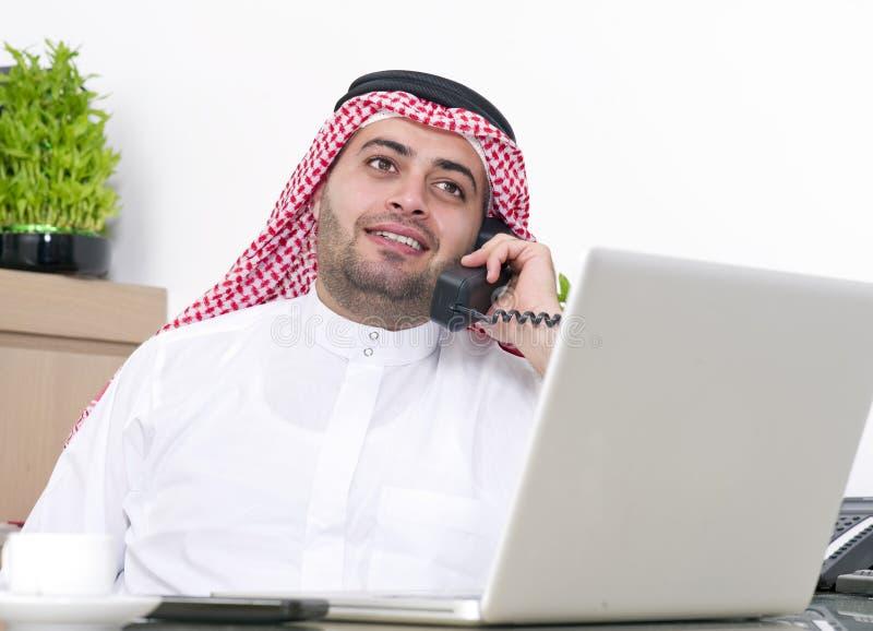 Homem de negócios árabe que usa o portátil e falando no telefone foto de stock royalty free