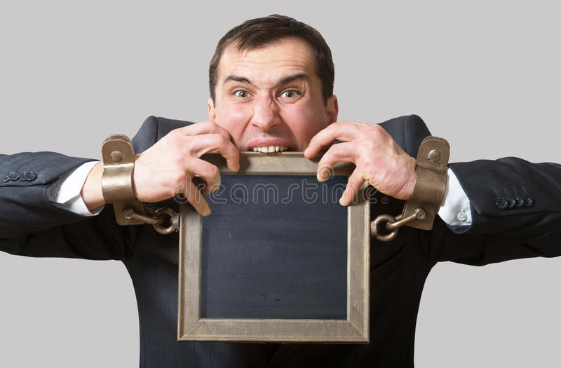 Homem de negócios acorrentado com uma placa imagens de stock royalty free