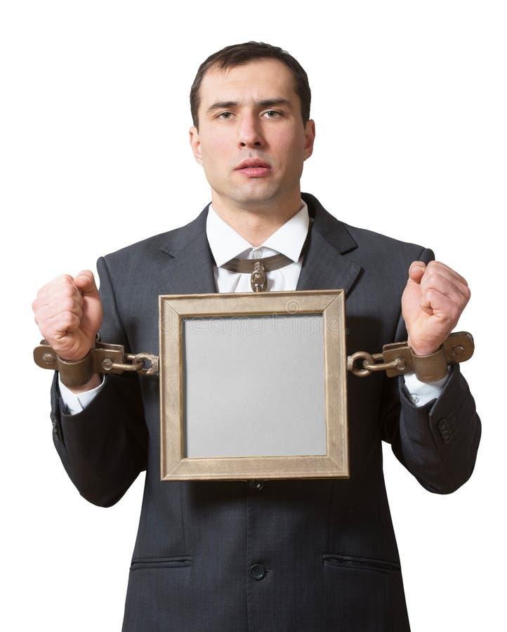Homem de negócios acorrentado com uma placa foto de stock royalty free