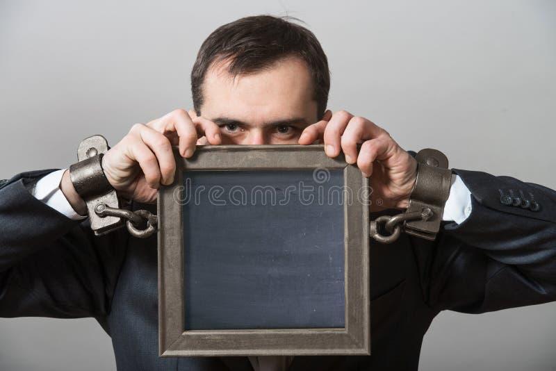 Homem de negócios acorrentado com uma placa foto de stock
