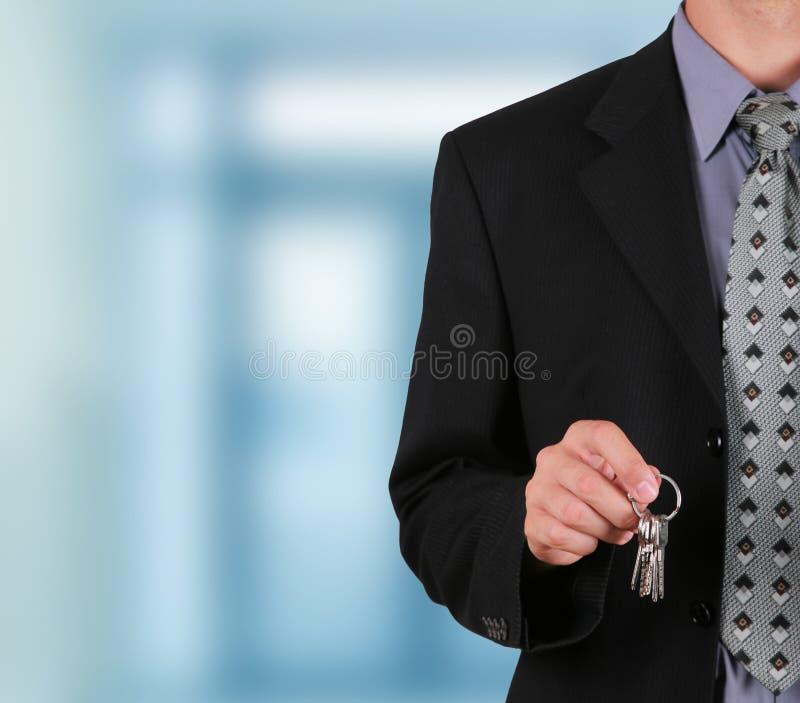 Homem de negócios adiando chave no seu corpo a corpo o imagens de stock royalty free