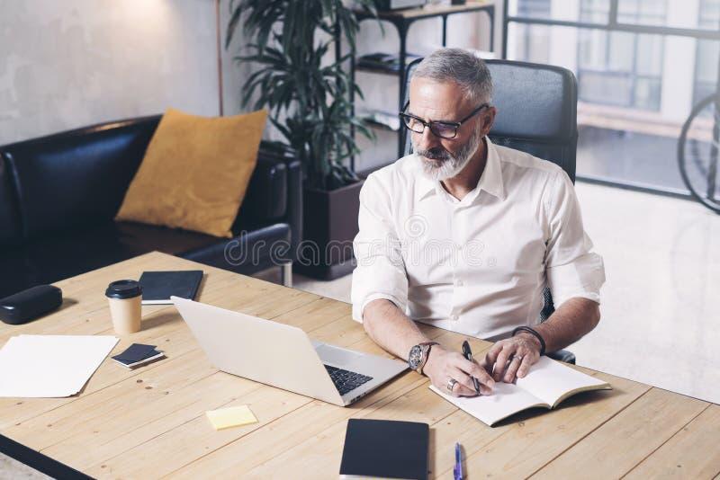 Homem de negócios adulto atrativo e confidencial que usa o laptop móvel e fazendo anotações ao trabalhar no de madeira fotografia de stock