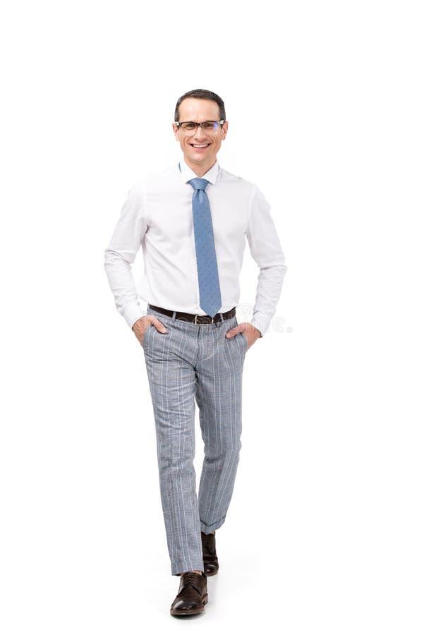 homem de negócios adulto considerável com mãos em uns bolsos que anda na câmera foto de stock