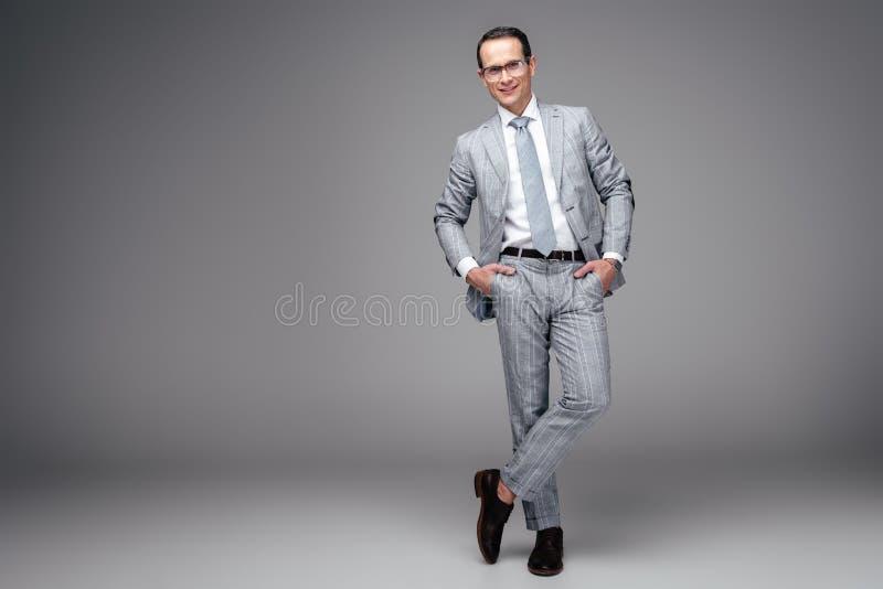 homem de negócios adulto considerável no terno à moda com mãos em uns bolsos foto de stock