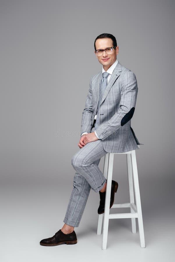 homem de negócios adulto considerável no terno à moda que senta-se na cadeira imagem de stock royalty free