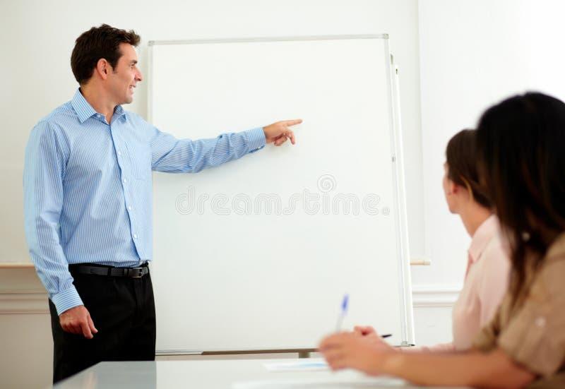Homem de negócios adulto considerável que aponta no whiteboard imagens de stock royalty free