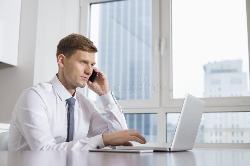 Homem de negócios adulto meados de na chamada ao usar o portátil em casa fotos de stock royalty free