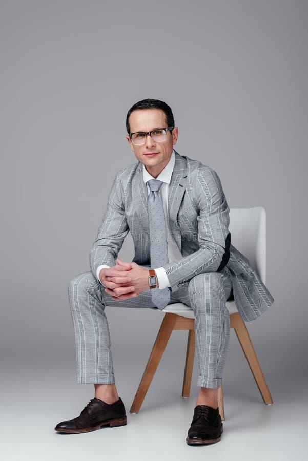homem de negócios adulto de sorriso no terno à moda que senta-se na cadeira e em olhar a câmera fotos de stock royalty free