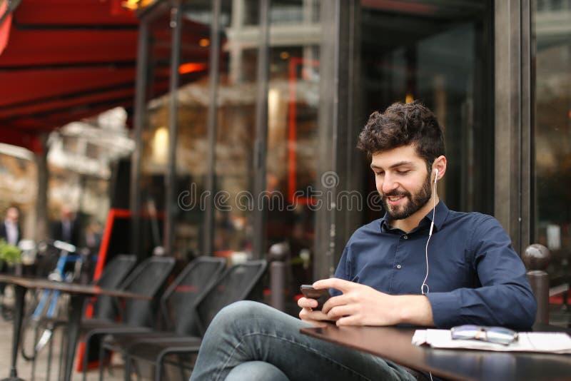 Homem de negócios afortunado que conversa pelo smartphone e que aprecia com succe foto de stock royalty free