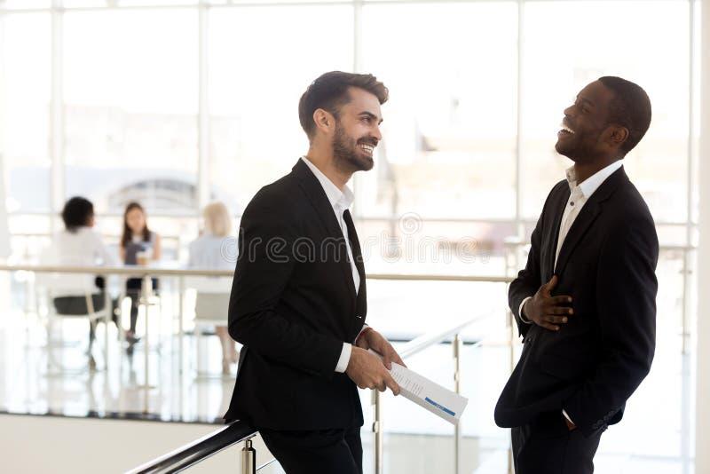 Homem de negócios africano alegre que ri do gracejo engraçado de caucasiano fotos de stock royalty free
