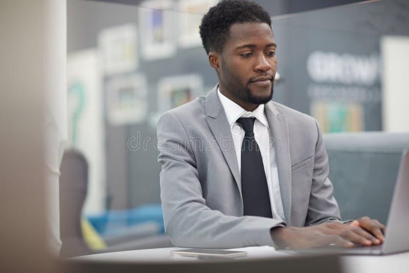 Homem de negócios africano bem sucedido no trabalho fotografia de stock royalty free