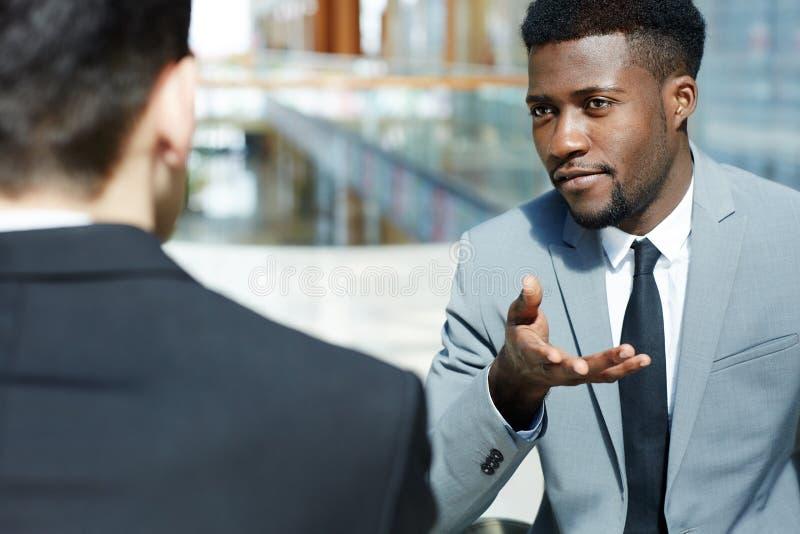 Homem de negócios africano considerável Discussing Work com sócios fotografia de stock royalty free