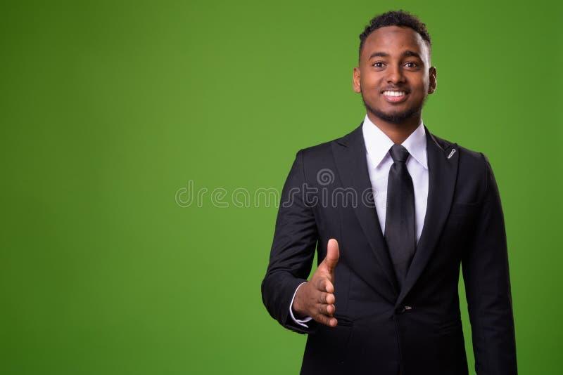 Homem de negócios africano considerável novo contra o fundo verde imagem de stock
