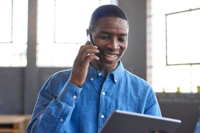 Homem de negócios africano de sorriso que usa uma tabuleta e um telefone celular no trabalho fotografia de stock royalty free