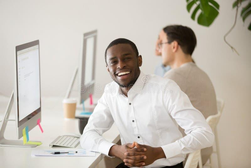 Homem de negócios africano feliz que olha a câmera que senta-se no local de trabalho imagens de stock