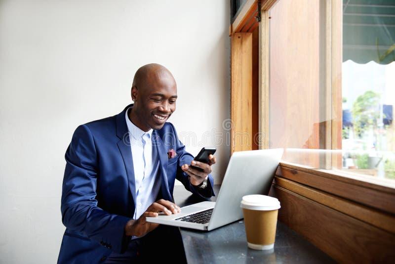 Homem de negócios africano feliz que usa o telefone no café imagem de stock royalty free
