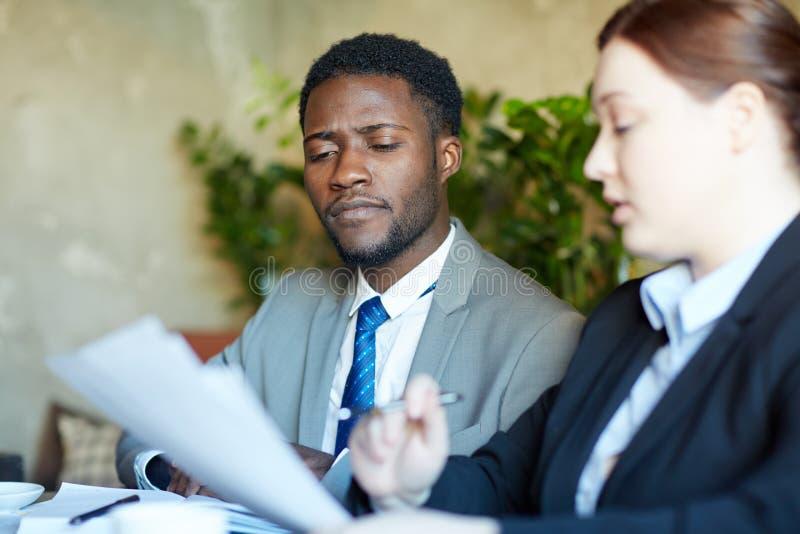 Homem de negócios africano focalizado Discussing Documents com colega imagem de stock royalty free