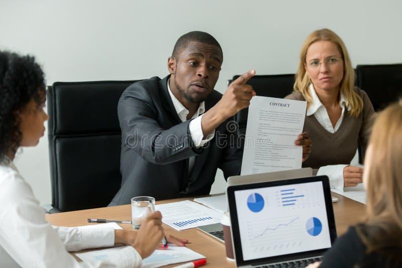 Homem de negócios africano irritado que discute sobre o contrato financeiro mau, fotos de stock