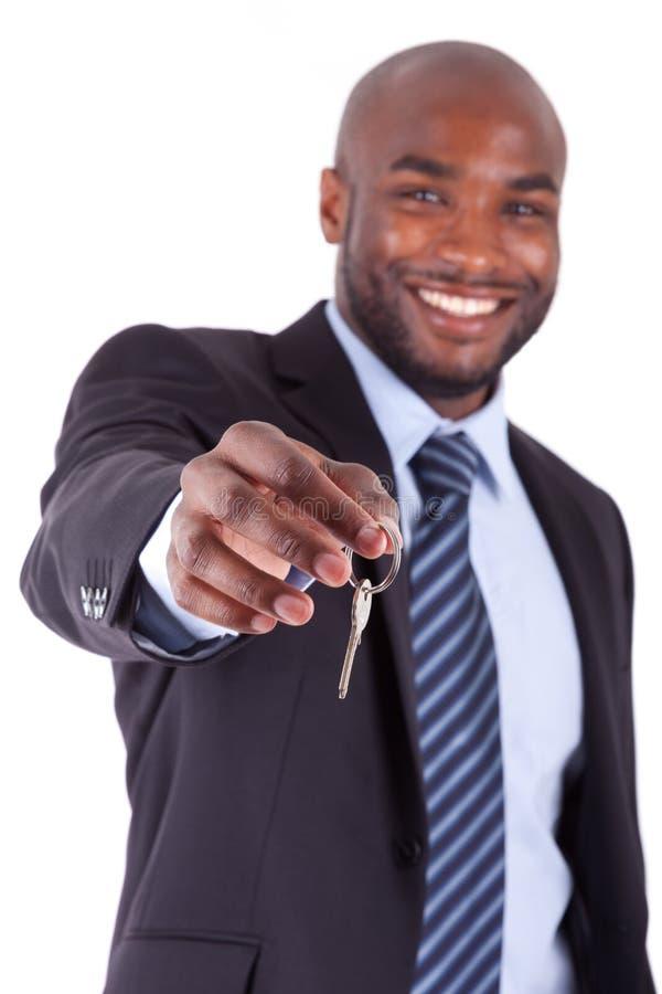 Homem de negócios africano novo que prende uma chave fotografia de stock