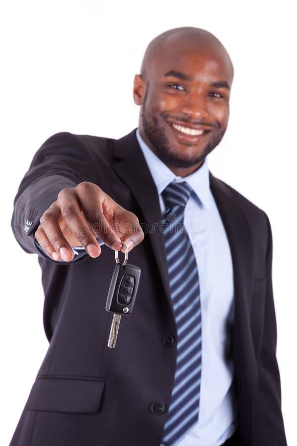 Homem de negócios africano novo que prende uma chave do carro foto de stock