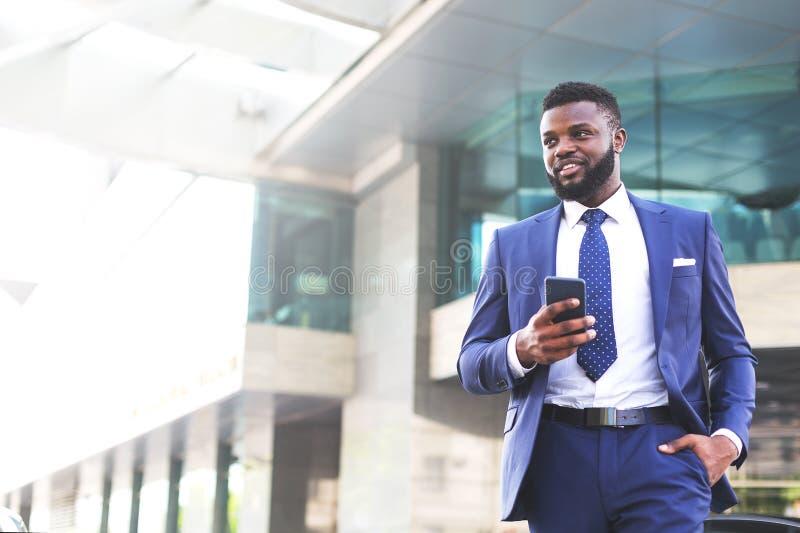 Homem de negócios africano novo que sae do escritório completamente da satisfação ao usar seu telefone Copie o espa?o fotos de stock royalty free