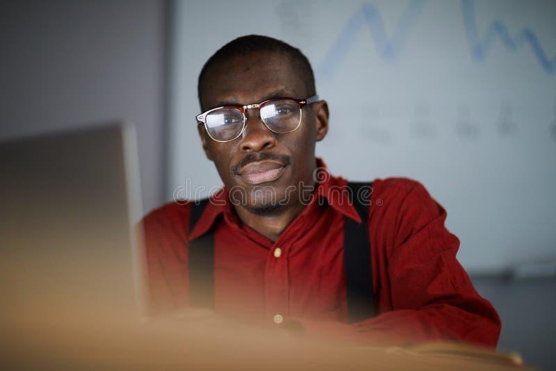 Homem de negócios africano Posing no escritório escuro imagem de stock royalty free