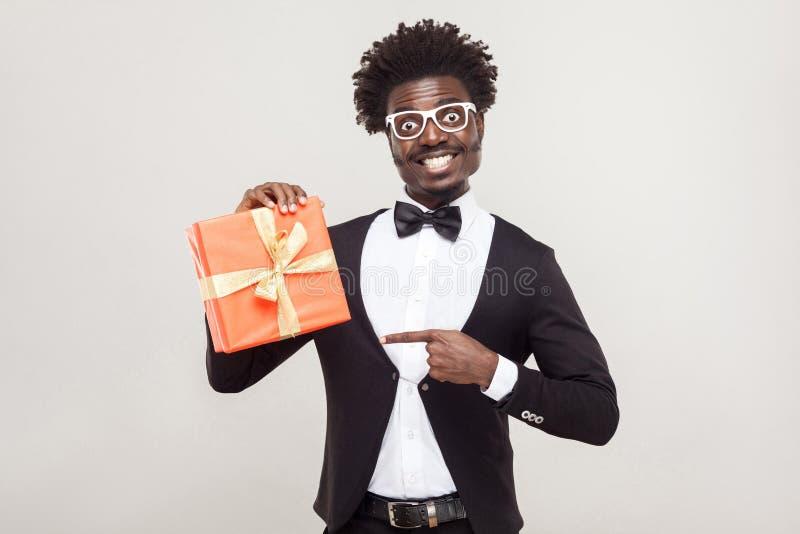 Homem de negócios africano que aponta os dedos na caixa de presente foto de stock royalty free