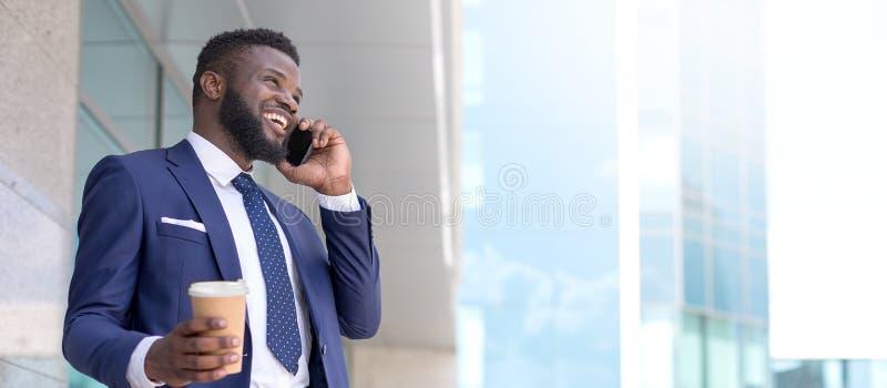 Homem de negócios africano que fixa felizmente um negócio com seu cliente durante seu período do almoço Copie o espa?o foto de stock royalty free