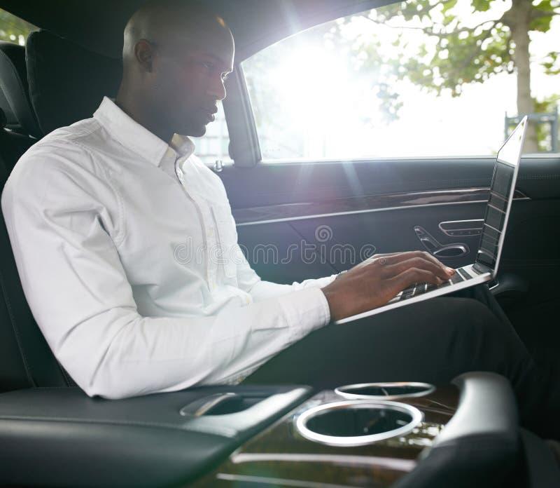 Homem de negócios africano que trabalha no portátil dentro de um carro fotografia de stock royalty free