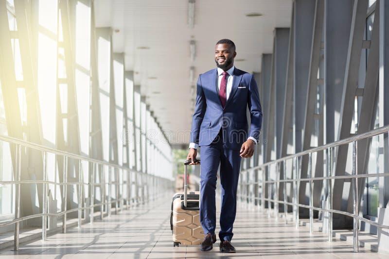 Homem de negócios africano de sorriso que leva uma bagagem no terminal de aeroporto imagens de stock