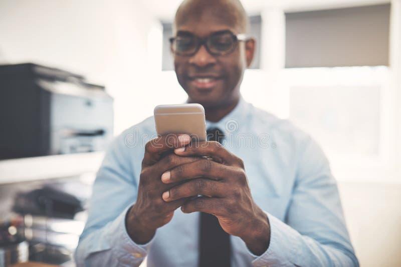 Homem de negócios africano de sorriso que usa um telefone celular em um escritório imagem de stock royalty free