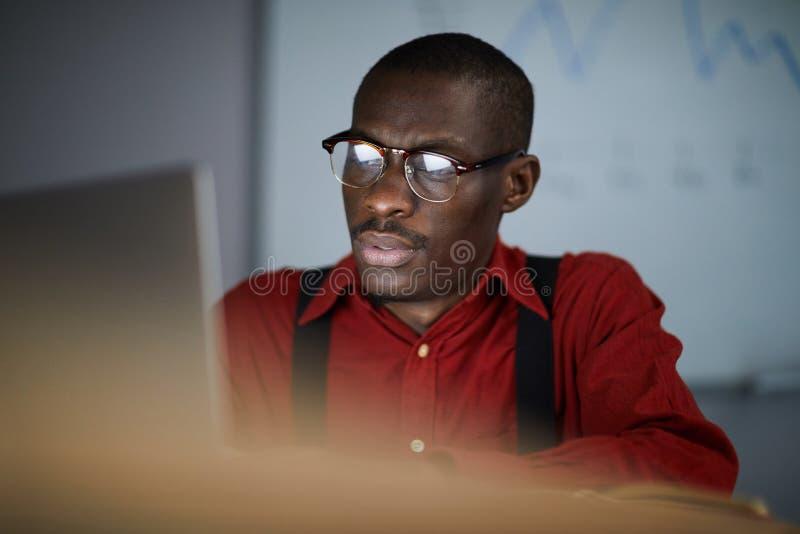 Homem de negócios africano Using Laptop no escritório escuro fotografia de stock royalty free