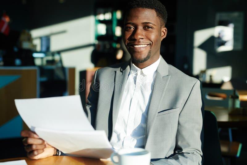 Homem de negócios africano Working com originais no café imagens de stock royalty free