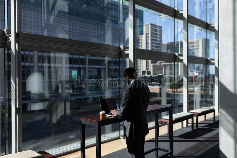Homem de negócios afro-americano com copo de café usando o portátil no escritório fotografia de stock royalty free